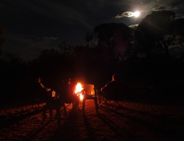Enjoying an evening under a full moon around a raging campfire