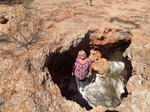 Deb under a rock overhang, viewed through a hole